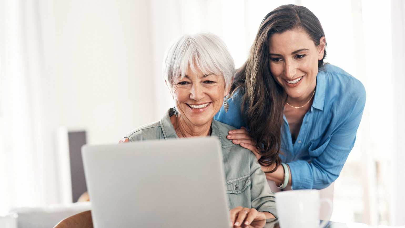 A mother overlooking her senior mother on a laptop.