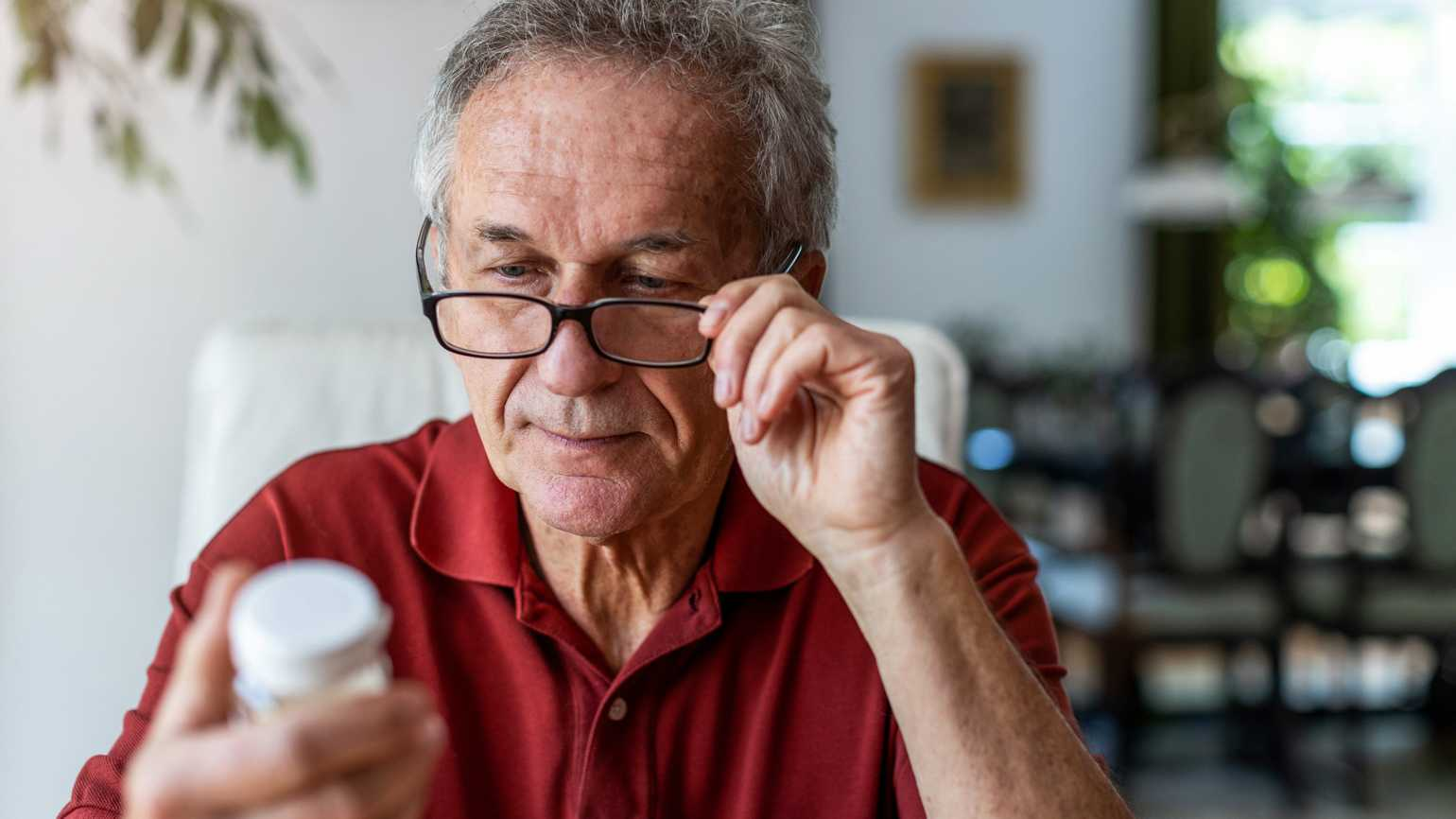 A senior man taking a look at a medication label; Getty Images