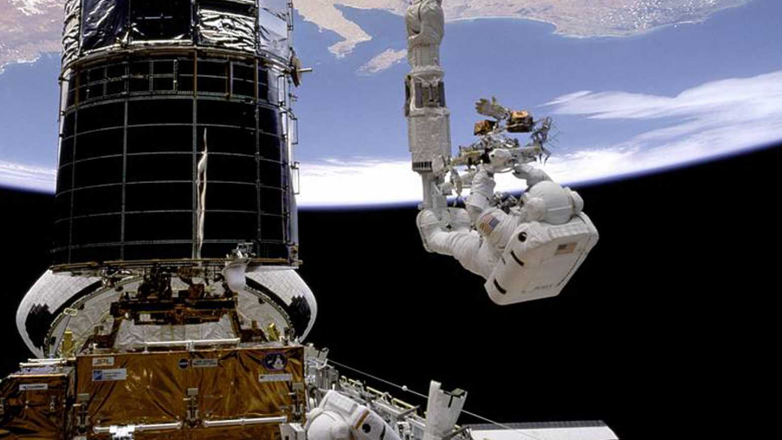 Guideposts: Astronaut F. Story Musgrave prepares to be elevated to the top of the Hubble Space Telescope.
