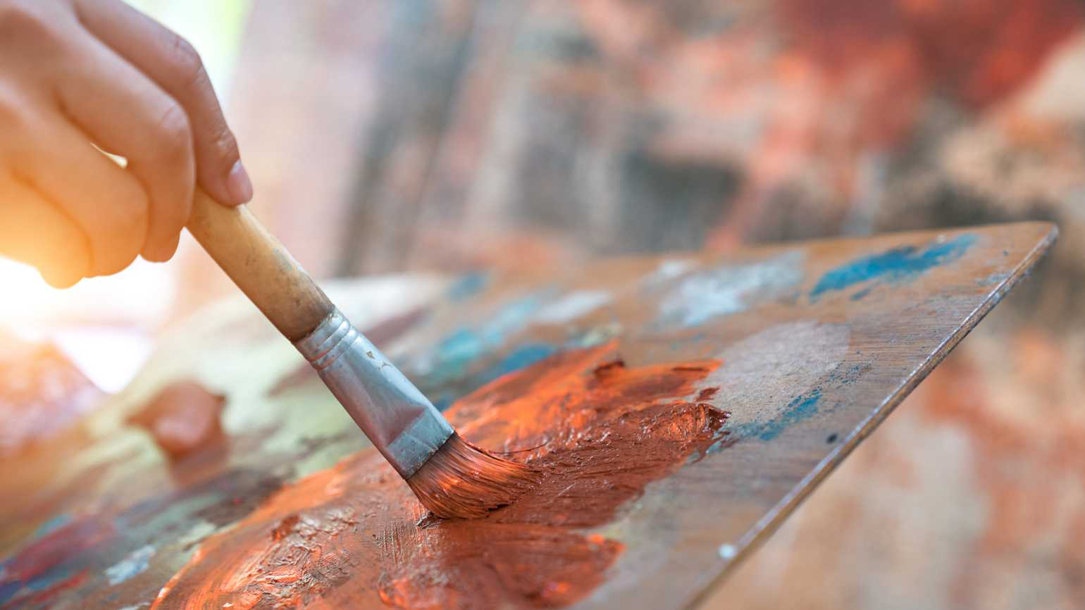 A close up of an artist painting on canvas.