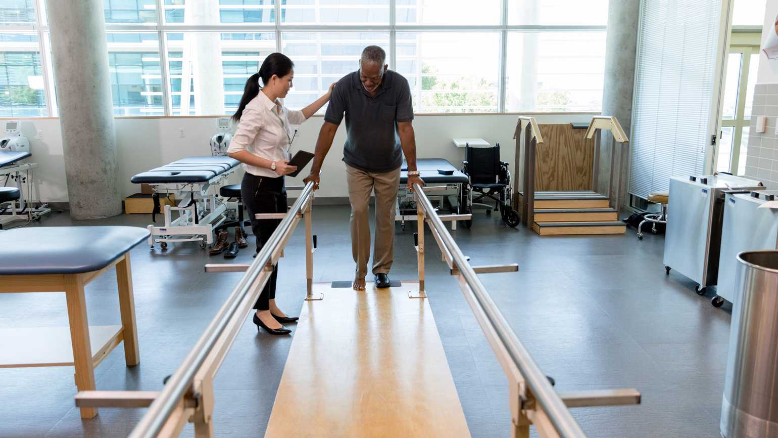An older man undergoes walking physical therapy with guidance.