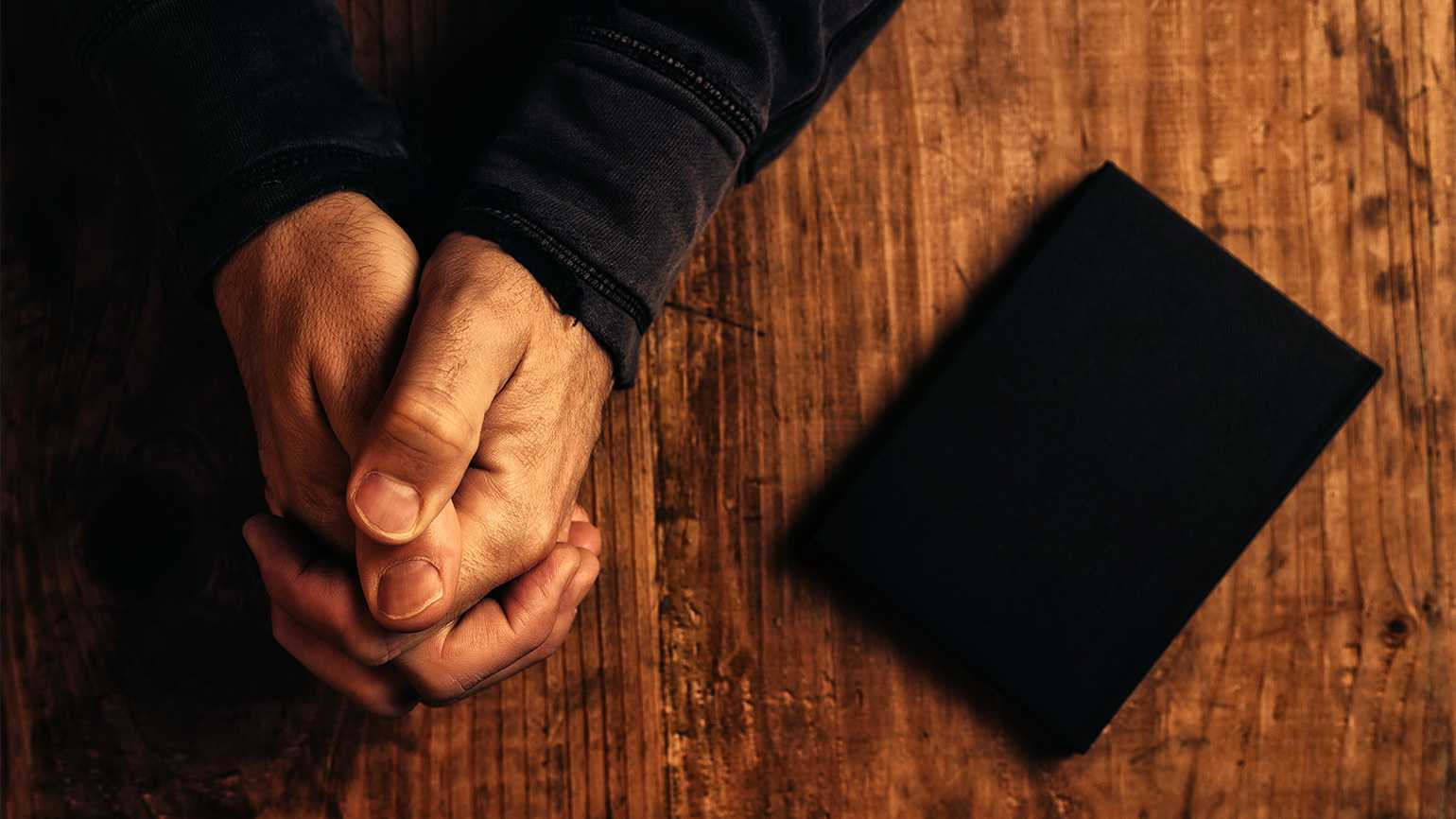 A man's hands clasped in prayer, with a Bible nearby