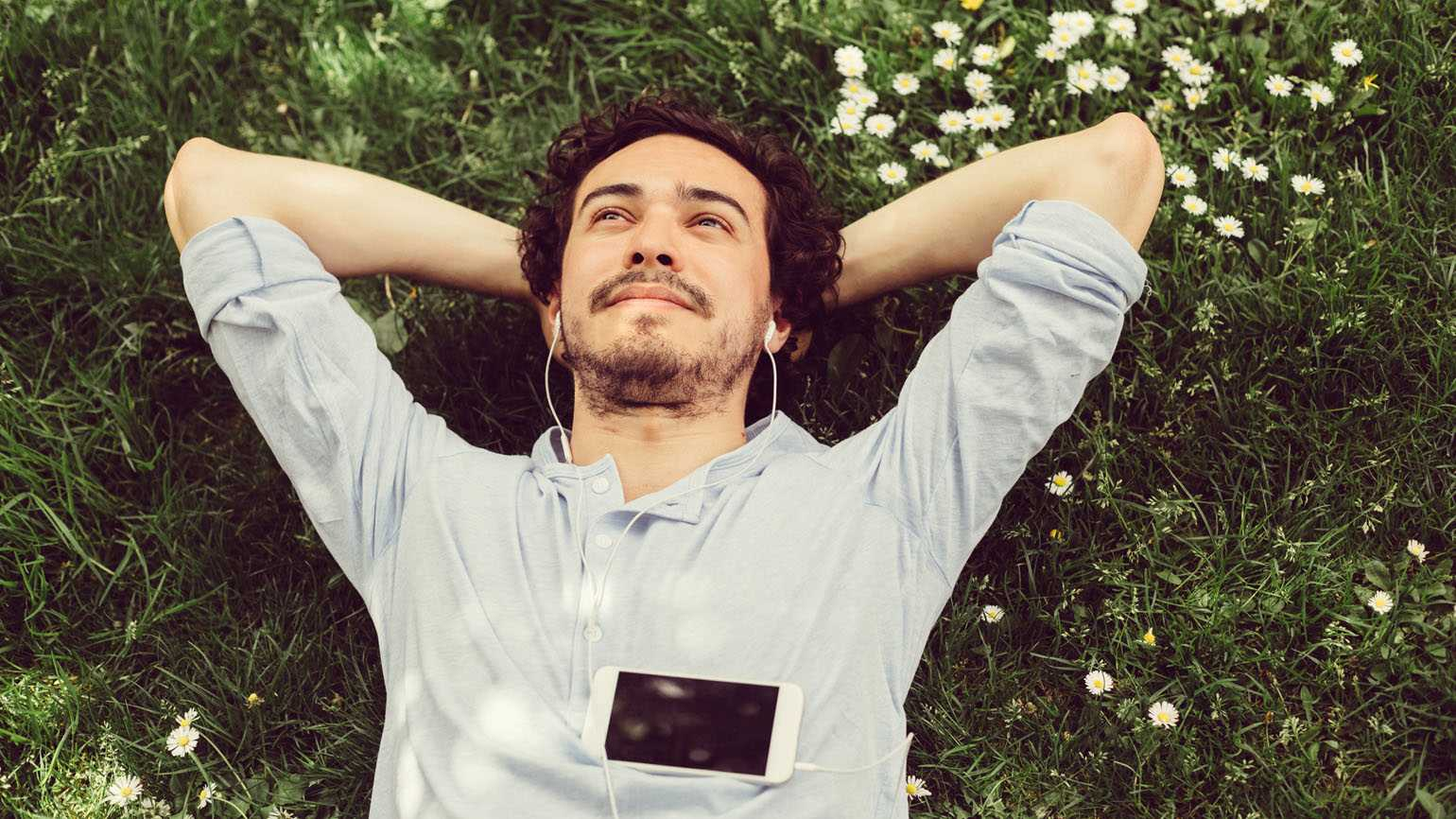A man relaxing on the grass while listening to music.