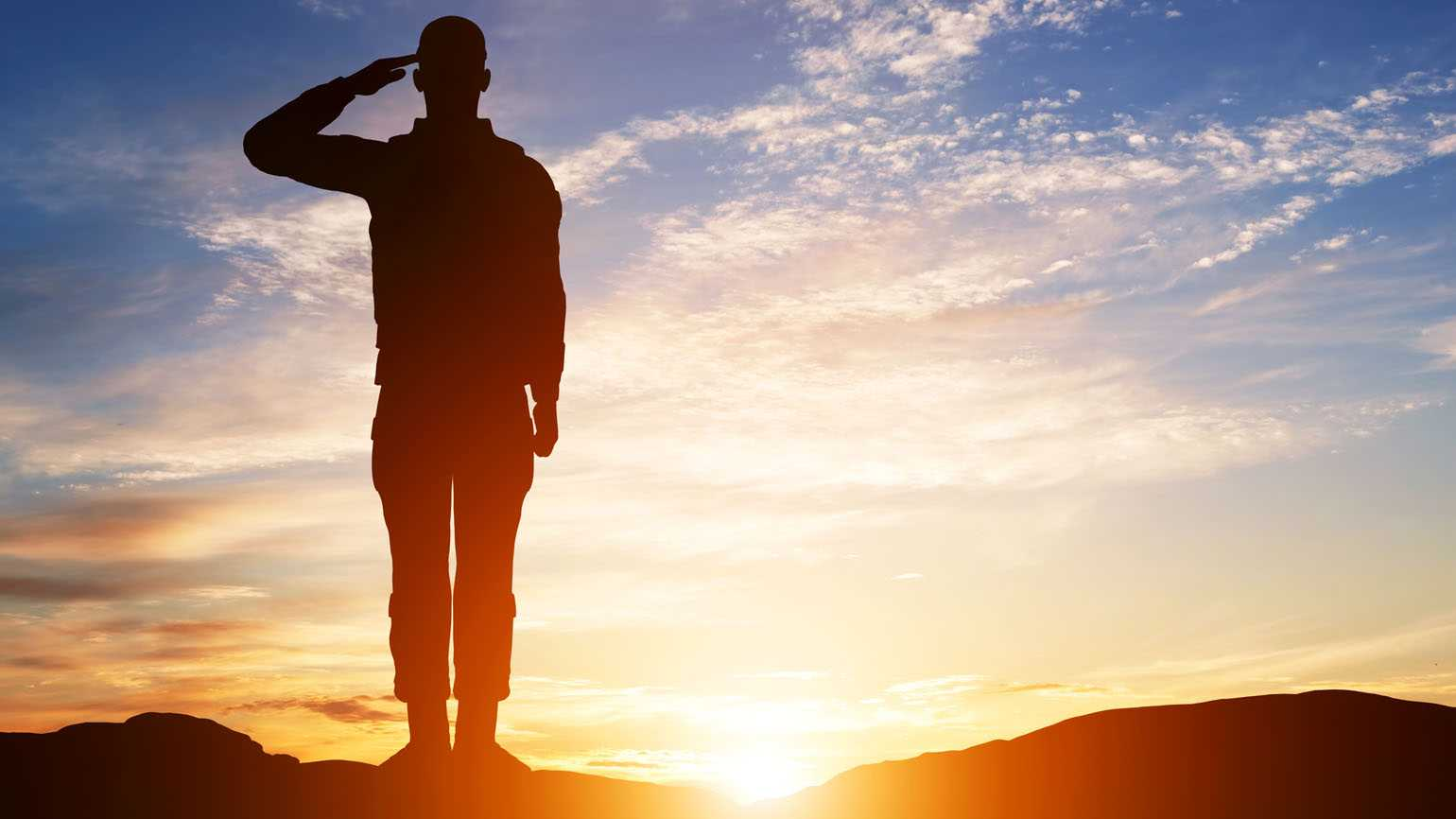 Soldier salute silhouette with sunset sky; Getty Images