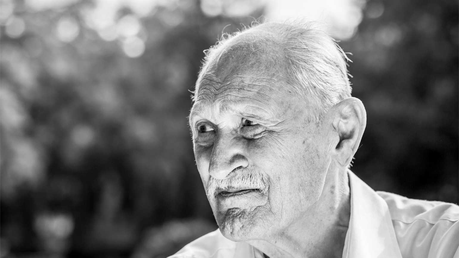 A black and white portrait of a senior veteran in a park.