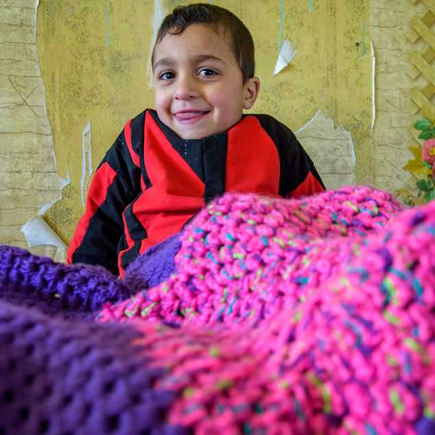 Four-year-old Serghik Mikayelyan sits under a Knit for Kids blanket