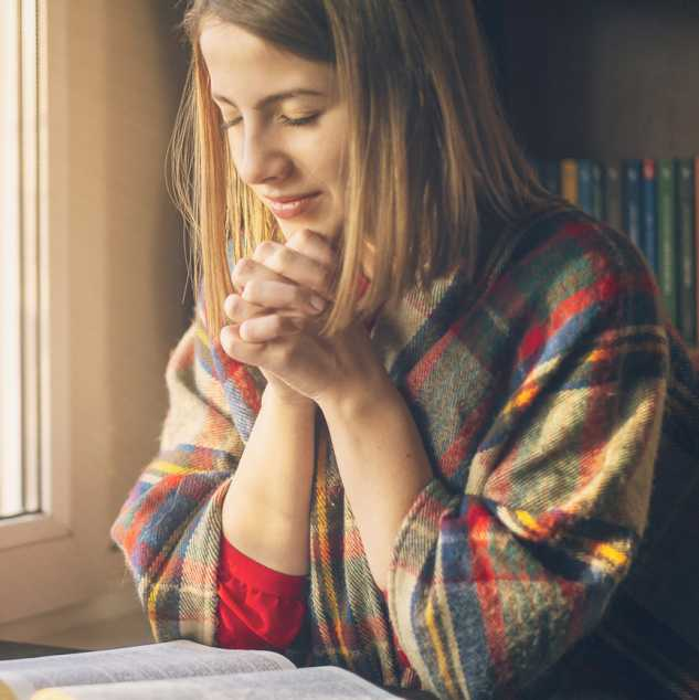 A young woman praying over a Bible.