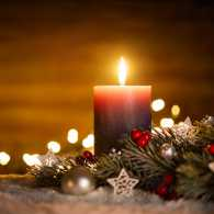 A lighted candle for the first Sunday of Advent
