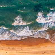 An aerial show of waves lapping on a beach