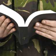 Guideposts: Soldier praying, Bible in hand.