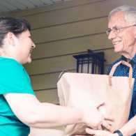 A woman brings foods to a senior neighbor