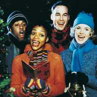 A quartet of carolers sing at the front door of a residence