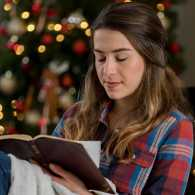 A woman reads her Bible during the Christmas season