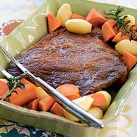 Brisket in a serving dish, surrounded by vegetables
