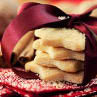 A stack of star-shaped sugar cookies with a Christmas ribbon tied around them