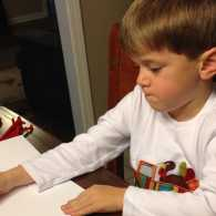 Cameron writes out his Christmas cards.