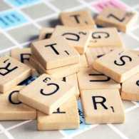 Close-up of Scrabble letter tiles jumbled on the Scrabble board.