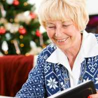 A woman smiles as she peruses her Christmas scrapbook.