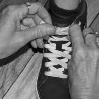 A photograph of a mother's hands tying a young boy's shoelaces.