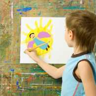 A boy paints at an easel.