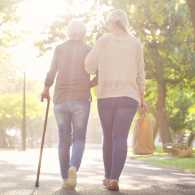 Daughter helping mother walk with a cane