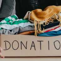 A woman gathers clothes to donate to charity