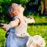 A young girl enjoys blowing bubbles