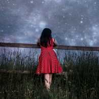 A young girl gazes up at a starry sky