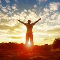 Man facing the sunrise with open arms