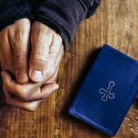 A man's hands clasped in prayer