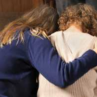 two women, one with arm around the other, heads bowed