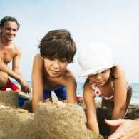 A family creates a sand castle on a sunny beach