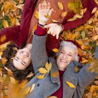 Grandmother and granddaughter lying on foliage and enjoy the autumn (Getty)