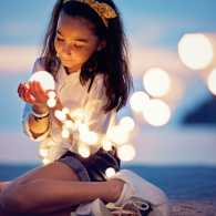 A young girl holding a string of brightly lit lanterns in prayer.