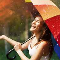 a laughing woman holds a rainbow colored umbrella in the rain