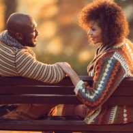 A loving couple gaze at each other while sitting on a park bench
