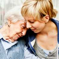 An adult daughter embraces her mother who has dementia