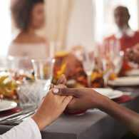 Family saying grace at Thanksgiving dinner table