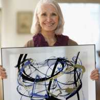A senior woman holding her artwork; Getty Images