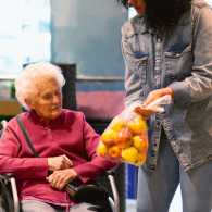 A woman in her golden years grocery shopping with the assistance of a caregiver.