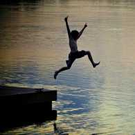 A boy leaps into a lake from a float/Melnotte/iStock/Getty Images Plus