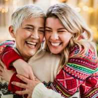 Two women hug in front of Christmas tree