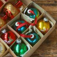A set of vintage Christmas ornaments in a box on a wooden table.