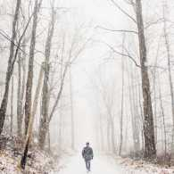 A figure of a man walking on a snowy path in the woods.