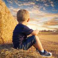 Young boy sitting on bales of straw and looking up into the sunset