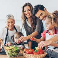 A happy family of parents, grandmother and children gather in the kitchen