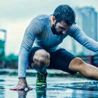 Man stretching in the rain