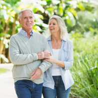 An older couple walking through a lush, green, scenic park.