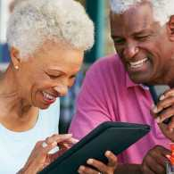 A mature couple use a tablet together