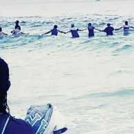 Rescuers form a human chain in dangerous water